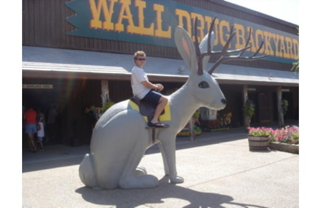 41 - Man riding a statue of a rabbit with antlers in South Dakota. South Dakota