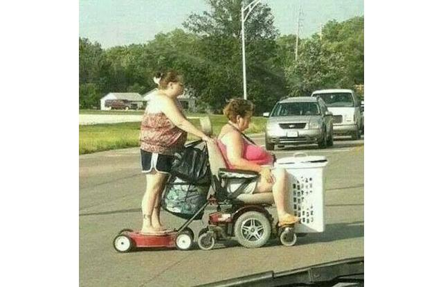 48 - Woman on lawnmower being pulled by woman in a wheelchair in West Virginia. West Virginia
