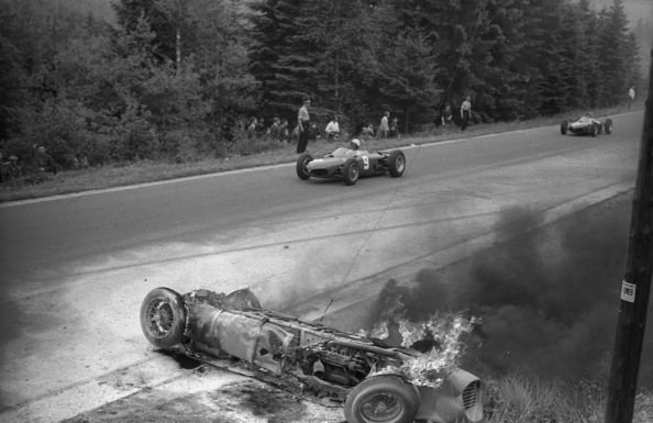 2 - A car sits on fire while other racers continue to race during the Belgian Grand Prix in 1962. The driver escaped with minor wounds.