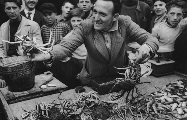 3 - A man sells live crabs at a market in Italy, 1950.