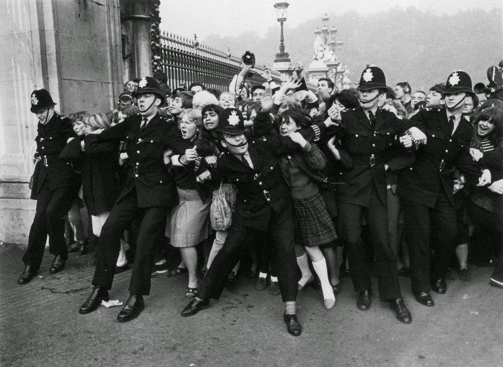 9 - Fans begin to break through police lines to try and see the Beatles who were receiving the Member of the British Empire (MBE) from the Queen at Buckingham Palace in London, England in 1965.