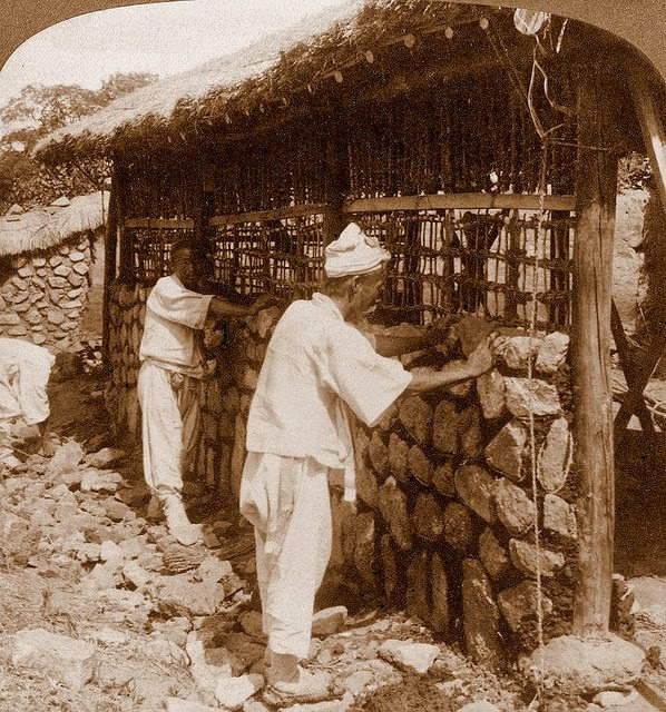 12 - Workers building the wall to a hut with stone in Korea, 1909.