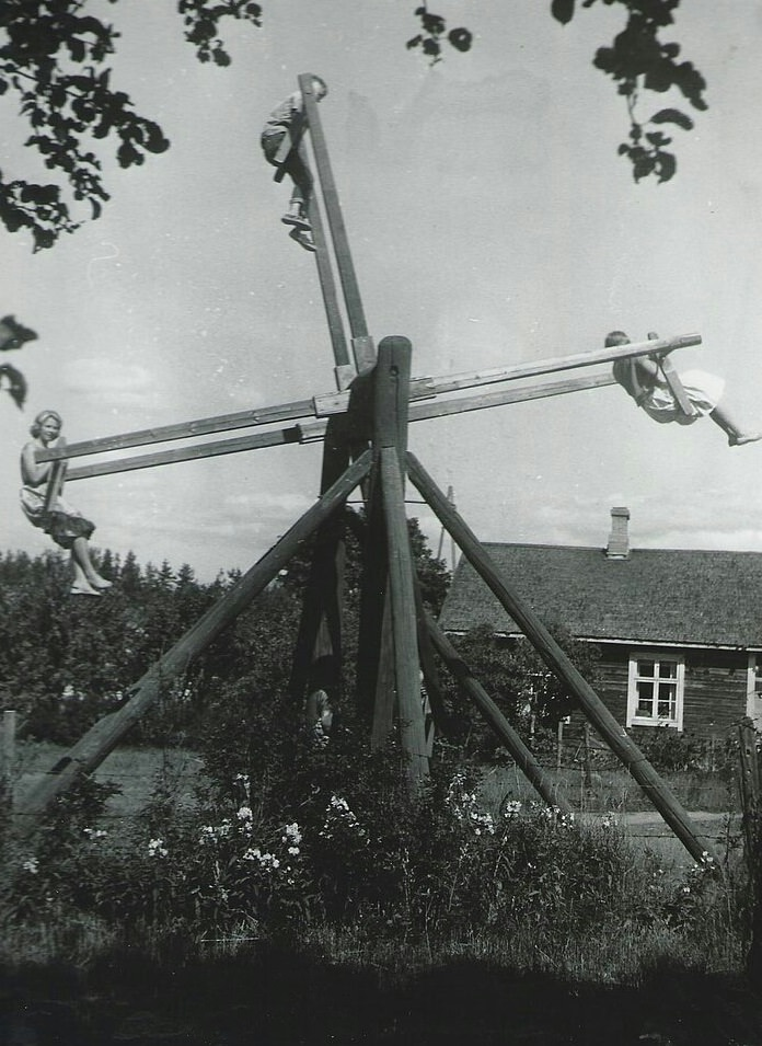 13 - A family plays on a unique four person homemade swing in Finland, 1954.