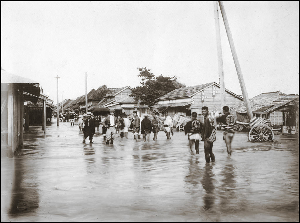 14 - People walk through flooded streets to go about their daily lives in Yokohama, Japan in 1908.