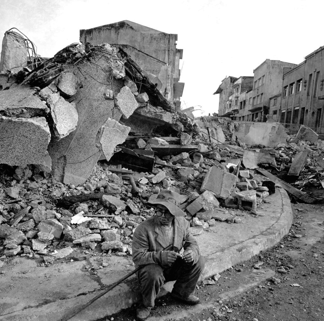 18 - A visibly shaken man sits on the curb in Valdivia, Chile after a massive earthquake rocked the city and much of the country, killing over 5,700 people in 1960.
