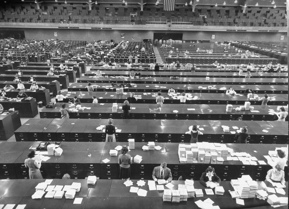 20 - FBI agents and secretaries review files at the overflowing archive at the DC Armory in Washington DC, US in 1945. The archive collected over 23 million individual cards and over 10 million fingerprint records during WWII. At one point they were adding around 400,000 new cards every month.