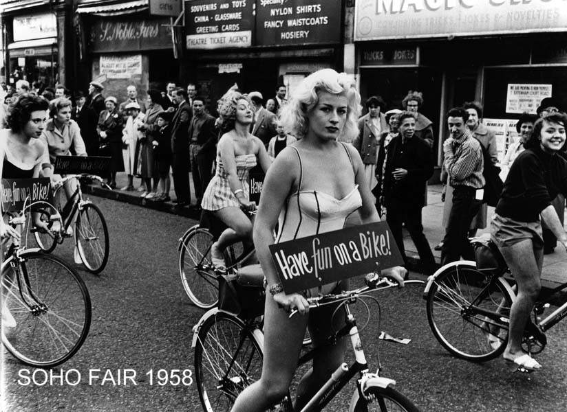 24 - Women ride bikes during the parade at the Soho Fair in London, England in 1958.