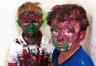 two young boys covered in paint