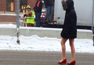 girl in the snow with no pants and red high heels