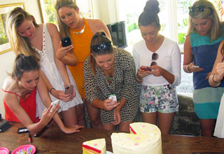 teen girls taking cell phone pictures of a cake