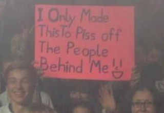 guy holding sign in a crowded audience that says: I only mode this to piss off the people behind me.