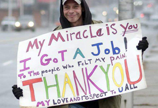 Homeless man happily holds a sign that says: My Miracle is you. I got a job! Thank you. My love and respect to u all.