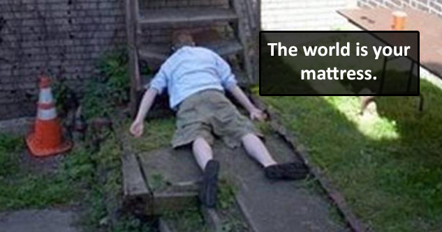 Guy sleeping on the ground with his face on the bottom stair. Caption reads: The world is your mattress.