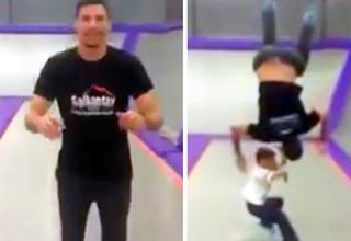 guy doing backflip on trampoline over little boy