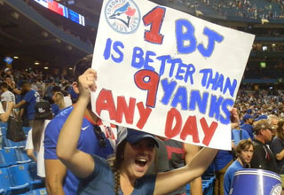 Woman in Blue Jays clothes holds a sign saying: 1 BJ is better than 9 yanks any day.