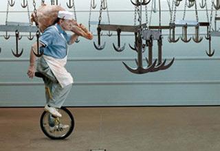 man on unicycle riding through sharp hooks