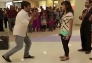Man in a crowded mall is about to propose to his girlfriend.