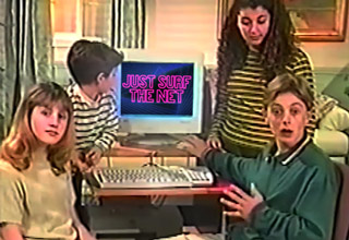 kids sitting around computer that says just surf the