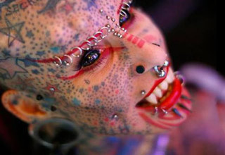girl with tons of piercings and body modifications