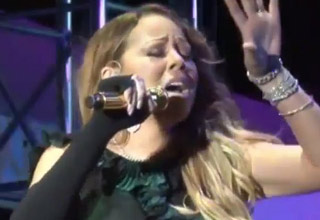 Mariah Carey in a live performance pretending to belt out tunes.