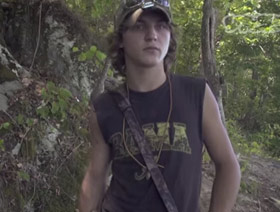 A young redneck stands in the forest.