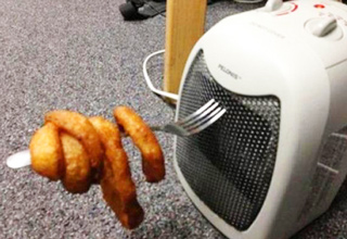 onion rings on a fork heated by a space heater