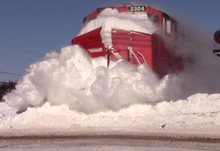 train plows through snow