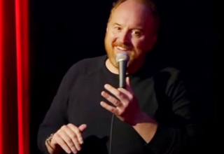 Louis CK smiling on stage