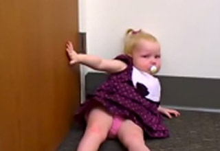 Toddler laying on ground throwing mega-tantrum at discovery of baby sister.