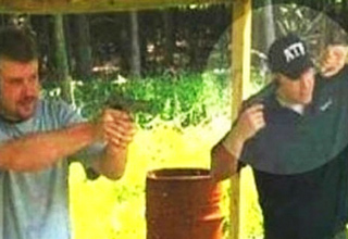two guys at a gun range one is covering his ear with