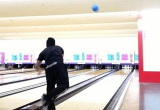 Guy throws a bowling ball.