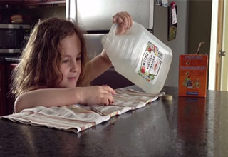 little girl pouring vinegar into baking soda volcano