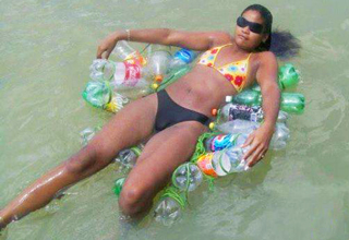 girl in bikini floating on empty plastic bottles