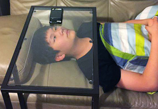 kid watching his phone while laying under a glass tabl