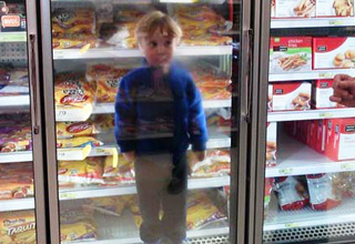 kid in the refrigerator at supermarket