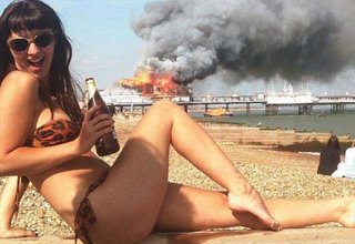 Hot woman in a bikini poses for camera in front of a burning boat in the background.
