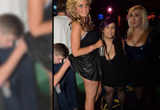 Three women pose for a picture in a nightclub, a crouching guy is lifting her skirt and looking at her butt.