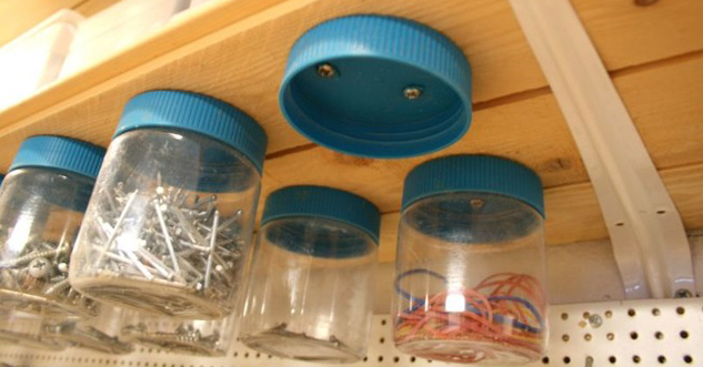 Jars screwed to the underside of a shelf. the jars are holding nails and things.