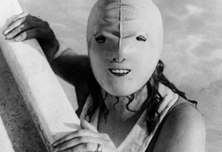 Woman in pool wearing a creepy swim mask that covers her entire face.