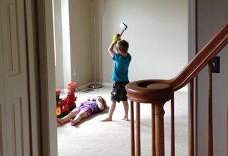 Kid holds a toy axe over his sister, who is laying on the carpet.