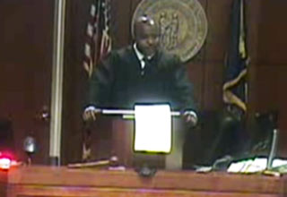 judge standing behind podium in courtroom