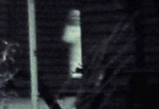 ghostly figure peers around the corner of a house