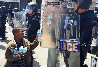 black kid giving water to riot police in