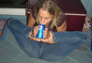 Hot girl drinking beer with her feet in a living