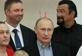 Steven Seagal doing bunny ears fingers behind Vladimir Putin and smiling at another g