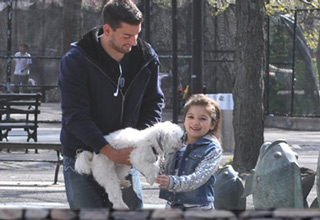 man holding white dog and little girl petting the dog