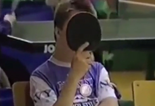 Boy covers his face with a ping pong paddle.