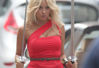 Hot woman walking through traffic and holding swords.