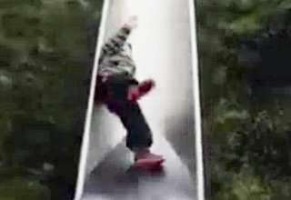 little kid takes a wild ride down a slide