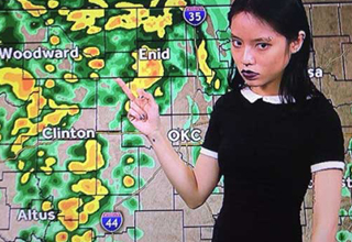 Girl uses her middle finger to give weather report. She is dressed like Wednesday from the Adam's Family and looks pissed.